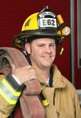 stock photo of firehose  - portrait of a happy smiling firefighter standing in front of fire engine in uniform holding a fire hose - JPG