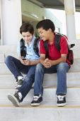 stock photo of pre-teens  - Pre teen boys with phone at school - JPG