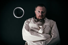 picture of madman  - insane man in his forties wearing a straitjacket standing in a cell of an asylum with the light from the hallway streaming in - JPG