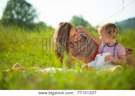 Pretty Young Mother Reading Book To Her Little Daughter