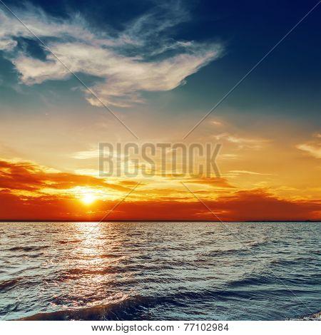 blue and orange sunset over darken sea
