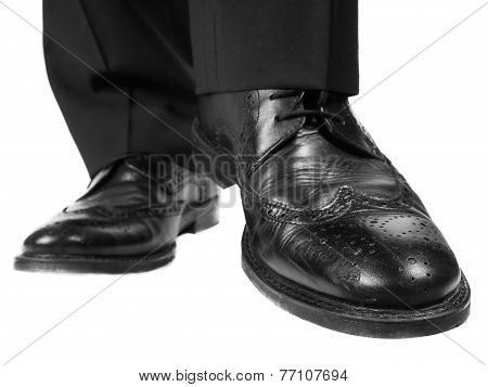 Person In Black Suit And Shoes Lifting One Foot