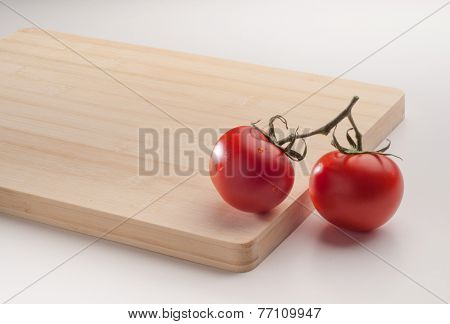 Two red tomatoes on a wooden cutting board.