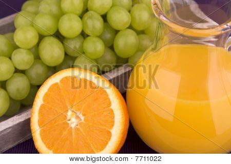 Orange juice in carafe with grapes