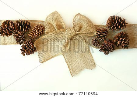 Burlap Christmas Bow With Pinecones Isolated On White Background