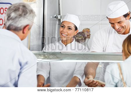 Happy female butcher looking at male customer in shop