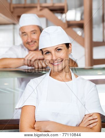 Portrait of happy mature female butcher with male colleague in background at butchery