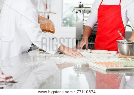 Midsection of chefs preparing ravioli pasta at counter in commercial kitchen