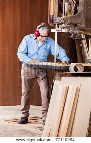 Full length of senior carpenter cutting wood with bandsaw in workshop