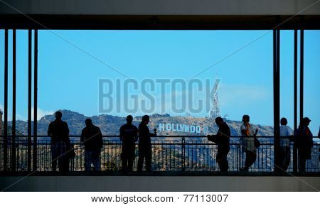 Los Angeles, CA - MAY 18: Tourists and Hollywood sign on May 18, 2014 in Los Angeles. Started as a small community, it evolved into the home of world famous film industry