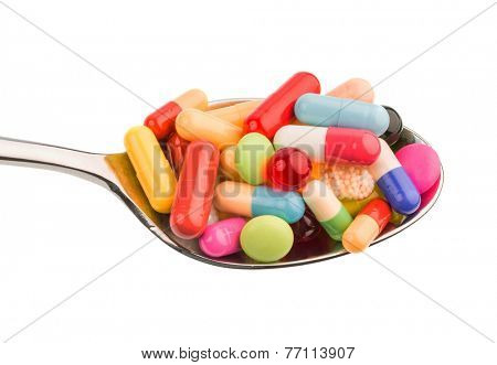 many colorful pills on a spoon. photo icon for tablets addiction and abuse of drugs.