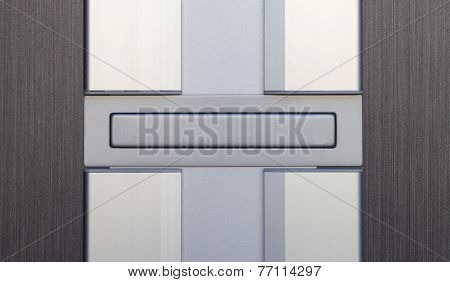 Sliver letterbox or mailbox and wood door at house