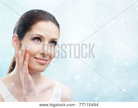 Woman applying cream on her face, winter background. The pursuit of beauty