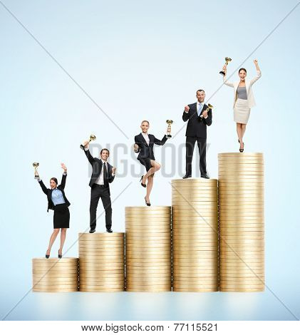 Business team with cups standing on the stairs of gold coins. Concept of business success