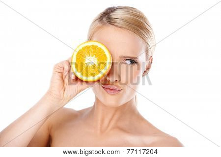 Close up Young Woman with Blond Hair Putting a Slice of Fresh Lemon Over her One Eye with Pouting Lips and Eye Looking to her Left Side. Isolated on White Background.