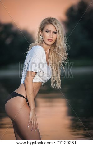 Portrait of young sexy blonde girl in bikini posing provocatively at the beach in sunset