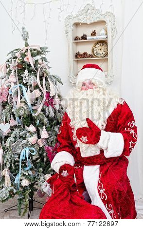 Saint Nicolas with a bag of gifts sits near a Christmas fir-tree