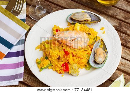 Paella served in plate on wooden table