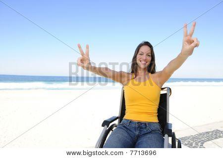 Feliz mujer en silla de ruedas al aire libre playa mostrando el signo de la victoria