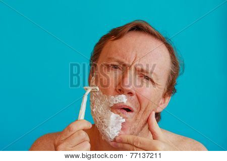 A Man Shaving His Beard With  Razor -blade