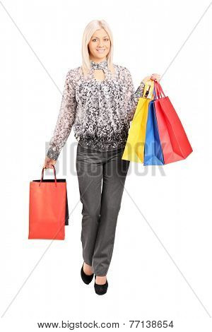 Full length portrait of a fashionable woman carrying shopping bags isolated on white background