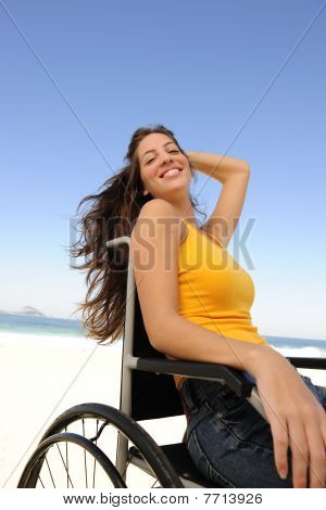 Woman In Wheelchair Enjoying Summer Vacation On The  Beach