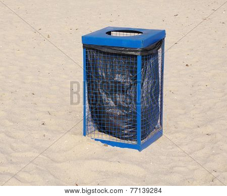 Metal Blue Garbage Dustbin On Beach Sand