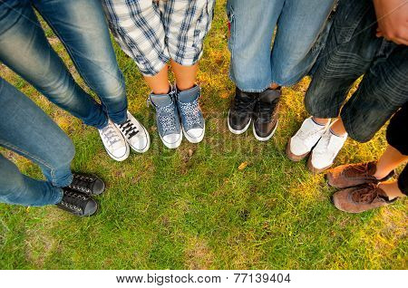 Legs and sneakers of teenage boys and girls