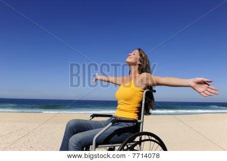 Woman In Wheelchair Enjoying Summer Vacation On The  Beach
