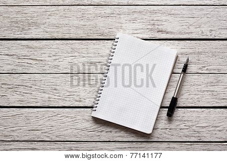Blank notepad with a pen on white wooden desk.