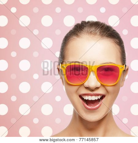 happiness, holidays, fashion and people concept - happy laughing teenage girl in shades over pink and white polka dots pattern background