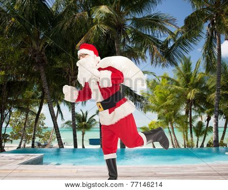 christmas, holidays and people concept - man in costume of santa claus running with bag over tropical beach and swimming pool background