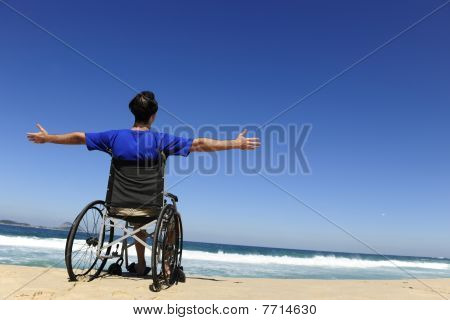 Man In Wheelchair Enjoying Summer Vacation On The  Beach