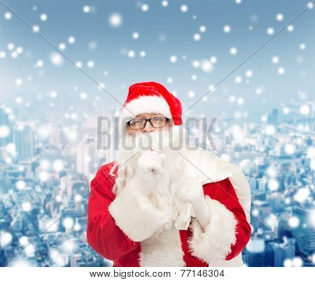 christmas, holidays and people concept - man in costume of santa claus with bag making hush gesture over snowy city background