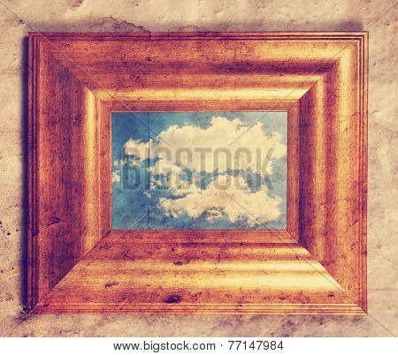 a distressed frame with a cloud in it toned with a retro vintage instagram filter
