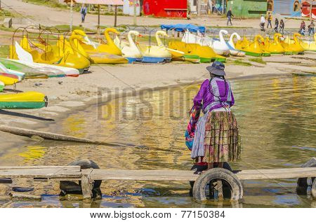 COPACABANA, BOLIVIA, MAY 7, 2014: Local woman in traditional attire on jetty in port (Titicaca lake)