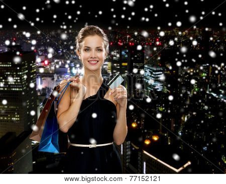 shopping, sale, banking, money and holidays concept - smiling woman in dress with shopping bags and credit card over snowy night city background