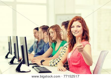 education, technology and school concept - smiling female student with classmates in computer class at school showing thumbs up