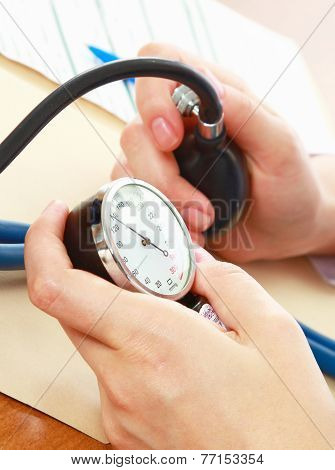 A doctor is measuring blood pressure with a tonometer