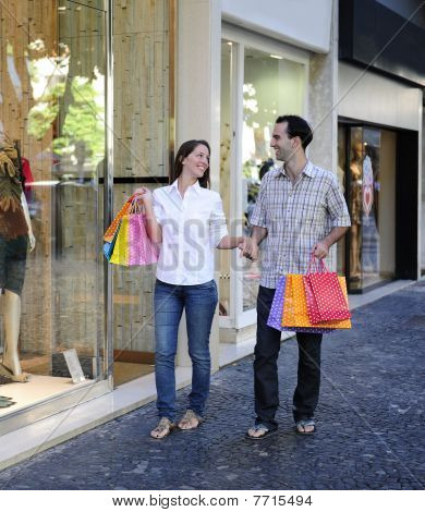Couple With Shopping Bags In Front Of A Store