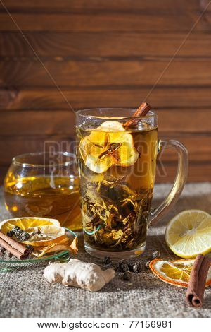 ginger tea with spices, honey, cinnamon, lemon and dried fruit on a linen background