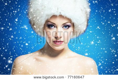 Portrait of young and beautiful woman in winter hat over blue background with a falling snowflakes