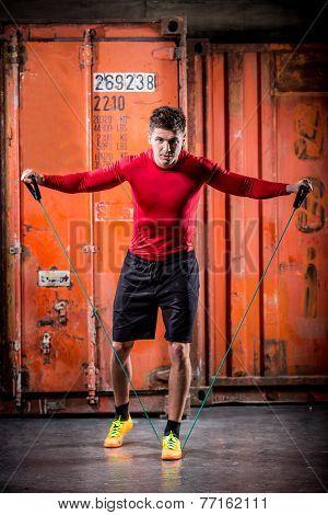 Muscular Handsome Man Pulls Rubber Bands
