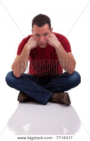 Upset Man Sitting Cross-legged On The Floor, Isolated  On White Background. Studio Shot