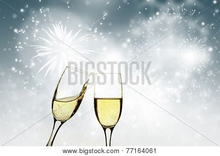 Glasses with champagne against holiday lights and fireworks
