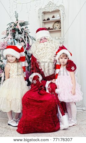 Saint Nicolas embraces two girls near a New Year tree