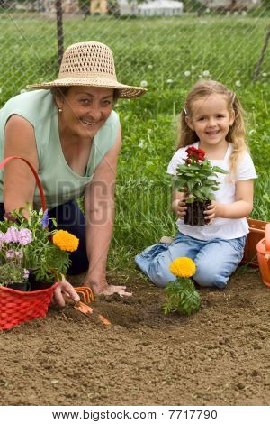 Grandmother Teaching Little Girl Gardening