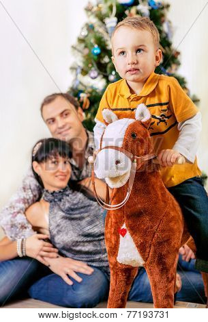 Little Boy On Toy Horse With His Parents Under The Chrismas Tree