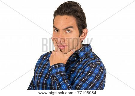handsome young latin man wearing a blue plaid shirt posing with hand on chin