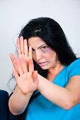 stock photo of domestic violence  - Abused scared woman with bruises on face sitting and showing stopping hands - JPG